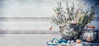 Концепция пасхи с установкой украшения весеннего времени: пук весны разветвляет с вишневым цветом, корзиной с яичками, лентой Стоковое Изображение