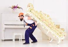 Концепция перестановки Курьер поставляет мебель в случае двигает вне, перестановка Человек с бородой, работник в прозодеждах и стоковая фотография