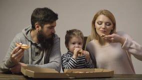 Концепция питания Вкусная пицца Мама, папа и сын едят пиццу совместно на белой предпосылке r видеоматериал