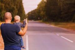 Концепция поездки Отец и сын пробуя остановить автомобиль на шоссе Семья заминк-пешая и останавливая автомобиль с большими пальца стоковое изображение