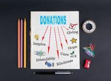 Концепция пожертвований На зажимах черной предпосылки тетради с прописями, карандашей, ручки, клейкой ленты и бумажных Стоковое Изображение RF