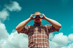 Концепция поиска приключения Человек разведчика при борода смотря через Bi Стоковое Фото