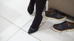 Концепция покупок - молодая женщина пробуя на черных высоких пятках в обувном магазине ноги сексуальные 4K кинематографическое видеоматериал