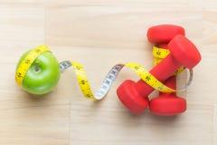 Концепция потери веса с свежим зеленым яблоком, измеряя лентой и гантелями Программа диеты фитнеса Угол взгляд сверху с spac экзе стоковое изображение