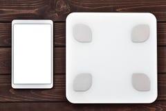 Концепция потери фитнеса и веса, белый масштаб и планшет на деревянном столе, взгляде сверху стоковое изображение rf