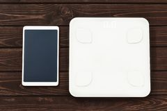 Концепция потери фитнеса и веса, белый масштаб и планшет на деревянном столе, взгляде сверху стоковые изображения rf