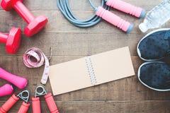 Концепция потери фитнеса и веса, гантели, веревочка скачки и измерять-лента на деревянной предпосылке Стоковые Фотографии RF