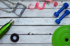 Концепция потери фитнеса и веса, гантели, рулетка, детандер, гимнастический круг и вода metal бутылка на деревянном столе top Стоковые Изображения