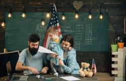 Концепция потехи Семья имеет потеху в классе Маленький ребенок и родители наслаждаются сложить бумажные самолеты Учить через поте стоковые изображения