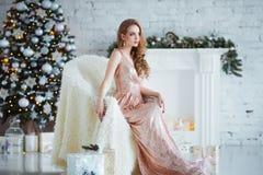 Концепция праздников, торжества и людей - молодая женщина в элегантном платье над предпосылкой интерьера рождества Изображение с Стоковое фото RF