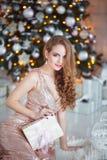 Концепция праздников, торжества и людей - молодая женщина в элегантном платье над предпосылкой интерьера рождества Изображение с Стоковая Фотография
