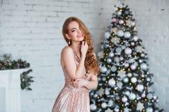 Концепция праздников, торжества и людей - молодая женщина в элегантном платье над предпосылкой интерьера рождества Изображение с Стоковое Изображение