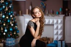 Концепция праздников, торжества и людей - молодая женщина в элегантном платье над предпосылкой интерьера рождества Стоковое Изображение RF