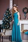 Концепция праздников, торжества и людей - молодая женщина в элегантном платье над предпосылкой интерьера рождества Стоковая Фотография RF