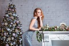 Концепция праздников, торжества и людей - молодая женщина в элегантном платье над предпосылкой интерьера рождества Изображение с Стоковое Изображение RF