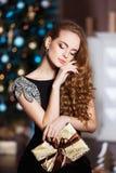 Концепция праздников, торжества и людей - молодая женщина в элегантном платье над предпосылкой интерьера рождества Стоковое Изображение