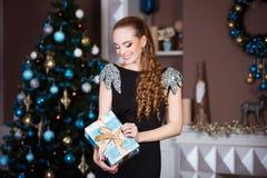 Концепция праздников, торжества и людей - молодая женщина в элегантном платье над предпосылкой интерьера рождества Стоковые Фото