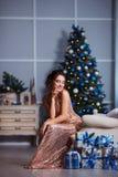 Концепция праздников, торжества и людей - молодая женщина в элегантном платье над предпосылкой интерьера рождества Стоковое фото RF