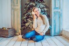 Концепция праздников, торжества и людей - молодая женщина над предпосылкой интерьера рождества Изображение с зерном Стоковые Изображения RF