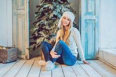 Концепция праздников, торжества и людей - молодая женщина над предпосылкой интерьера рождества Изображение с зерном Стоковое Фото