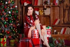 Концепция праздников, торжества и людей - молодая усмехаясь женщина в красном свитере над предпосылкой интерьера рождества Стоковое Изображение RF