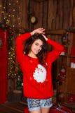 Концепция праздников, торжества и людей - молодая усмехаясь женщина в красном свитере над предпосылкой интерьера рождества Стоковые Изображения