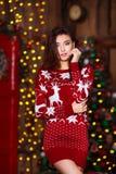 Концепция праздников, торжества и людей - молодая усмехаясь женщина в красном свитере над предпосылкой интерьера рождества Стоковое Фото
