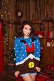 Концепция праздников, торжества и людей - молодая усмехаясь женщина в свитере над предпосылкой интерьера рождества Стоковое Фото