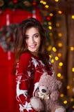 Концепция праздников, торжества и людей - молодая усмехаясь женщина в красном свитере над предпосылкой интерьера рождества Стоковые Фотографии RF