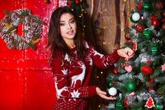 Концепция праздников, торжества и людей - молодая усмехаясь женщина в красном свитере над предпосылкой интерьера рождества Стоковая Фотография