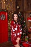 Концепция праздников, торжества и людей - молодая усмехаясь женщина в красном свитере над предпосылкой интерьера рождества Стоковое фото RF