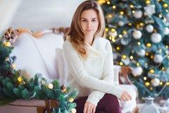 Концепция праздников, торжества и людей - молодая усмехаясь женщина в свитере над предпосылкой интерьера рождества Стоковые Изображения