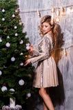 Концепция праздников, торжества и людей Портрет усмехаясь молодой женщины украшая рождественскую елку стоковое изображение