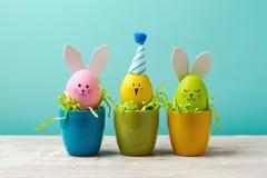 Концепция праздника пасхи с милыми handmade яичками, зайчиком, цыпленоками и шляпами партии в чашке стоковые изображения