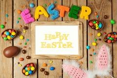 Концепция праздника пасхи с яичками шоколада и рамка фото на деревянной предпосылке Стоковое Фото