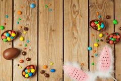 Концепция праздника пасхи с яичками шоколада и ушами зайчика на деревянной предпосылке Стоковые Изображения RF