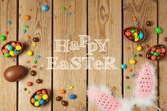 Концепция праздника пасхи с яичками шоколада и ушами зайчика на деревянной предпосылке Взгляд сверху сверху Стоковые Изображения