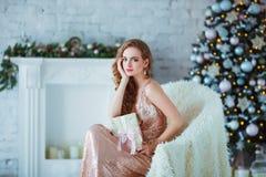 Концепция праздников, торжества и людей - молодая женщина в элегантном платье над предпосылкой интерьера рождества Изображение с Стоковые Изображения RF
