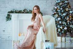 Концепция праздников, торжества и людей - молодая женщина в элегантном платье над предпосылкой интерьера рождества Изображение с Стоковая Фотография RF