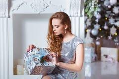 Концепция праздников, торжества и людей - молодая женщина в элегантном платье над предпосылкой интерьера рождества Стоковые Изображения