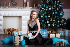 Концепция праздников, торжества и людей - молодая женщина в элегантном платье над предпосылкой интерьера рождества Стоковая Фотография