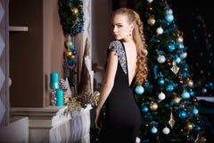 Концепция праздников, торжества и людей - молодая женщина в элегантном платье над предпосылкой интерьера рождества Стоковое Фото