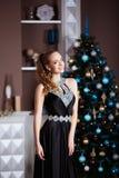 Концепция праздников, торжества и людей - молодая женщина в элегантном платье над предпосылкой интерьера рождества Стоковые Фотографии RF
