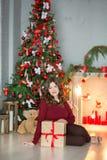Концепция праздников, торжества и людей - молодая женщина в элегантном платье над предпосылкой интерьера рождества Изображение с  Стоковые Фотографии RF
