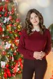 Концепция праздников, торжества и людей - молодая женщина в элегантном платье над предпосылкой интерьера рождества Изображение с  Стоковое Фото