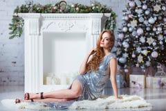 Концепция праздников, торжества и людей - молодая сексуальная женщина в элегантном платье над предпосылкой интерьера рождества Стоковая Фотография