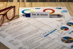Концепция представления вклада запасов 10 лучших с диаграммами и диаграммами на деревянной доске Стоковая Фотография