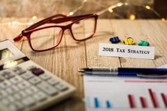 Концепция представления вклада стратегии 2018 налогов с диаграммами и диаграммами на деревянной доске Стоковое Изображение