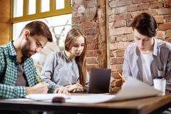 Концепция проекта дела представления нового Группа в составе молодые сотрудники обсуждая идеи друг с другом в современном офисе стоковое изображение