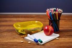 Концепция пролома школьного обеда с здоровой коробкой для завтрака и школьные принадлежности на деревянном столе, селективном фок Стоковая Фотография